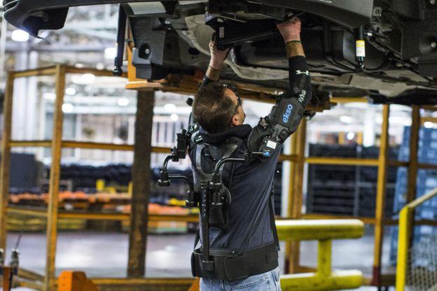 Hombre con un exoesqueleto reparar un auto.
