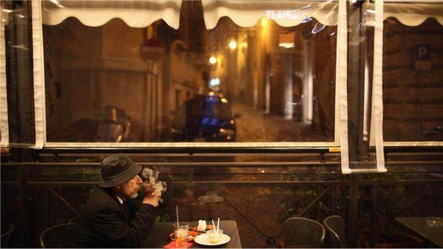Homem fuma em café na Europa
