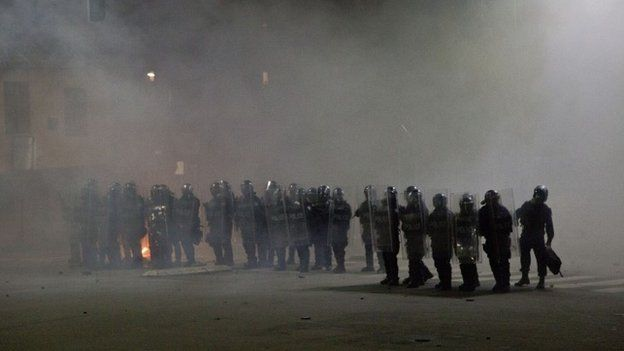 Kosovo police officers in riot gear stand in a cloud of tear gas in Kosovo capital Pristina as clashes broke out after the arrest of a prominent opposition politician Albin Kurti on Monday, Oct. 12, 2015.