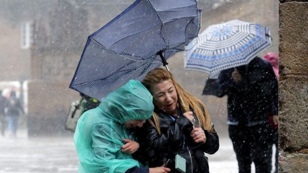 "Tourists protect themselves from the rain and the wind as the squall ""Miguel"" hits Santiago de Compostela, Spain, 06 June 2019"