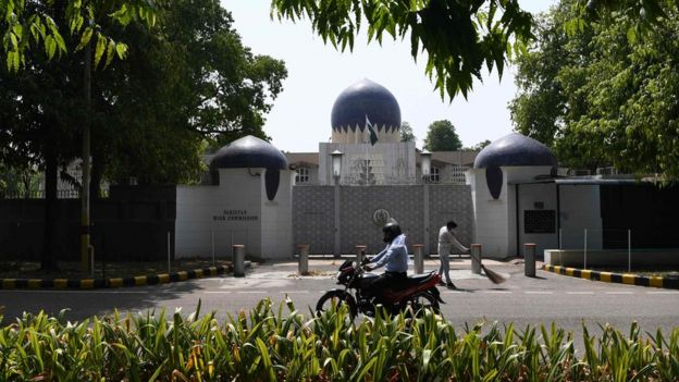 A motorist rides past the main gate of the Pakistan High Commission in Delhi, 1 June