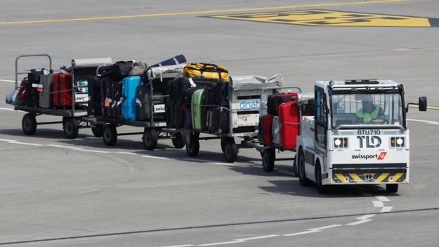 Truck pulling luggage trailers on airport runway