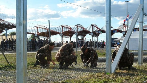 Hungarian soldiers raise a fence on the Croatian-Hungarian border