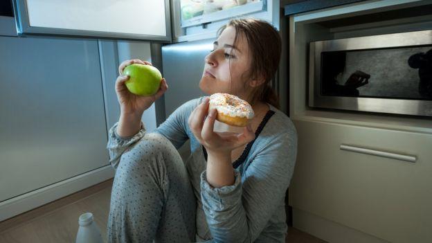 Mulher pensando se come uma maçã ou donuts