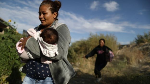 An immigrant mother crosses the US southern border with a baby in her arms.
