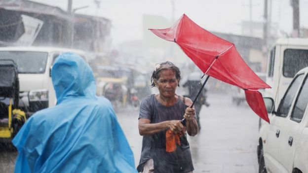 A woman clutches an umbrella amid heavy rain in the Philippines