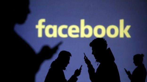Personas con el móvil frente a un letrero de Facebook