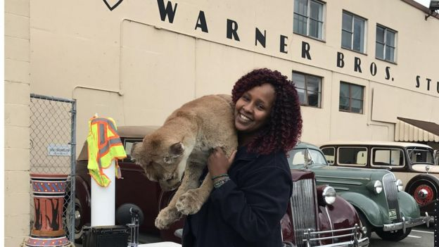 Ubah Mohamed carrying a lion cub outside a cinema studio