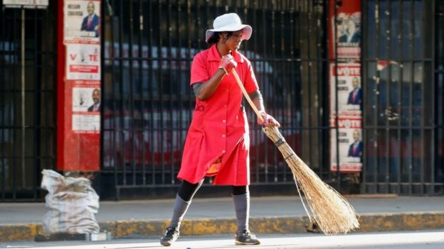 A woman sweeps the street outside the opposition Movement for Democratic Change (MDC) headquarters in Harare, Zimbabwe, 2 August 2018