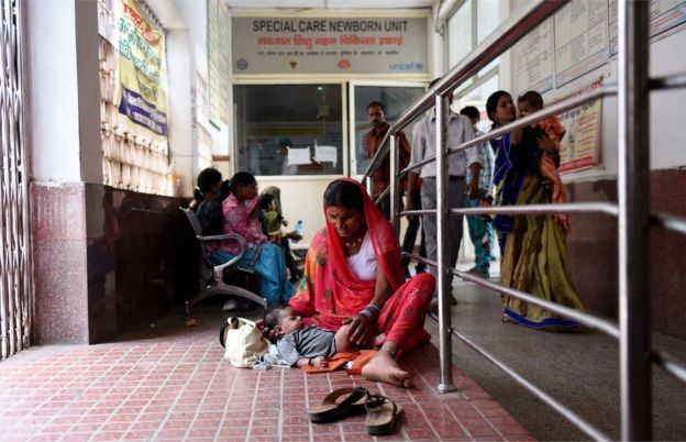 An Indian woman sits in a corridor with her child, outside a special care newborn unit, at a government hospital
