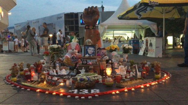 Drvena pesnica usmerena ka nebu ispred koje stoji fotografija Davida Dragičevića okružena desetinama upaljenih sveća. Avgust 2018, Banjaluka.