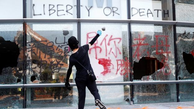 Protester throwing brick at a building