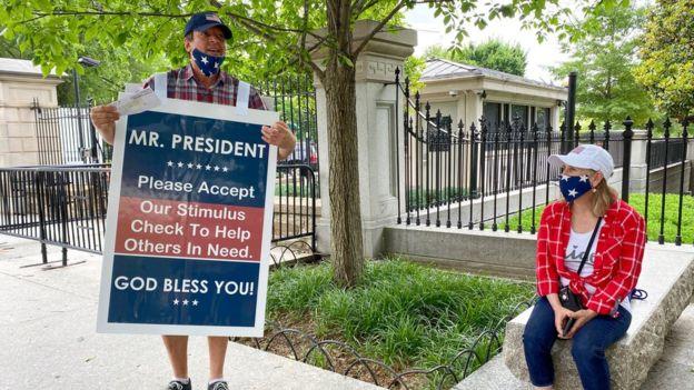 Un hombre con un cartel en el que ofrece su cheque al presidente Trump para que se lo dé a alguien más necesitado