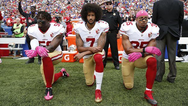 Eli Harold, Colin Kaepernick and Eric Reid kneeling during the national anthem