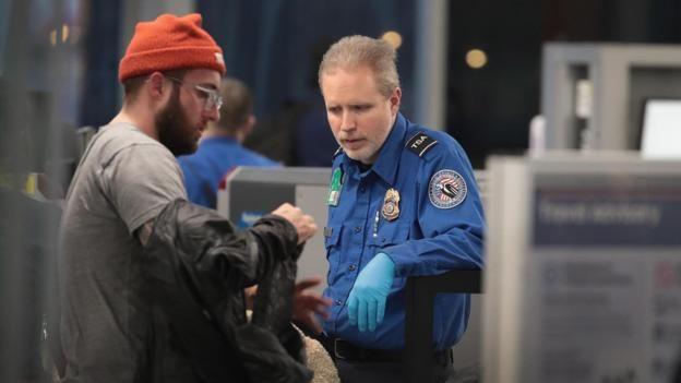Một nhân viên của Cơ Quan Quản Lý An Ninh Giao Thông (TSA) sàng lọc hành khách và nhân viên sân bay tại Sân Bay Quốc Tế O'Hare ở Chicago diễn ra