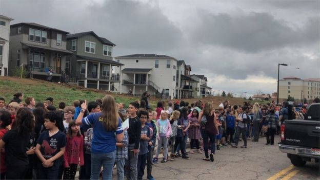Students and staff wait outside near the STEM School in Colorado