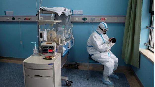 Profissional inteiramente paramentado segura bebe em sala de hospital, com vários aparelhos ao lado