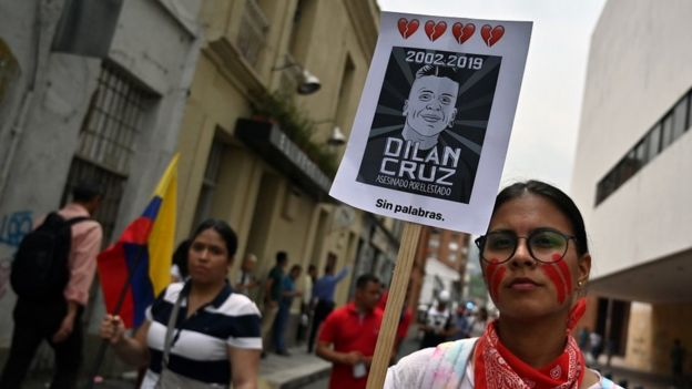 A demonstrator holds a poster of the late student Dilan Cruz - who died due to injuries from a police shot on November 23 - during a march against the government of Colombian President Ivan Duque during a national strike, in Cali on November 27, 2019.