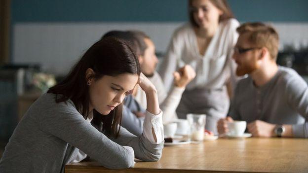 Pessoa solitária ao lado de pessoas conversando