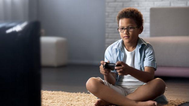 Um menino jogando videogame