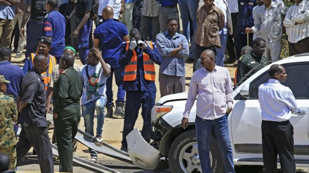 Crowds at the scene of the blast surrounding one white damaged vehicle in Khartoum, Sudan - 9 March 2020
