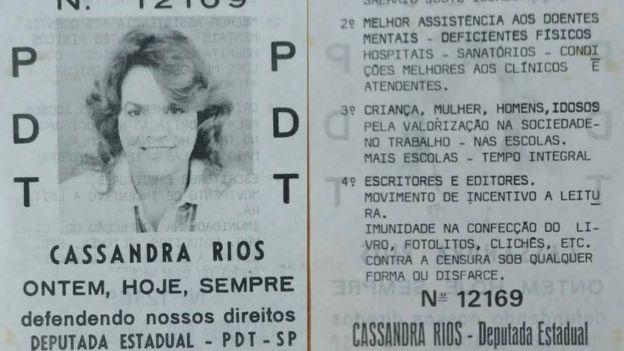 Santinho de campanha mostra foto de Cassandra sorrindo e frase 'Ontem, hoje, sempre defendendo nossos direitos'