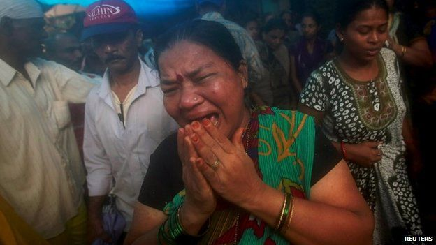 Wife of Mansingh, 52, who died after consuming bootleg liquor, cries outside their house in a slum in Mumbai, India, June 20, 2015.