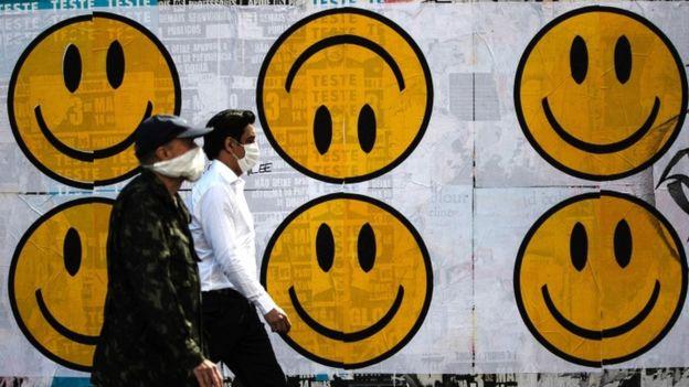 Dois pedestres com máscaras passam em frente a cartazes com carinhas felizes, uma delas de cabeça pra baixo