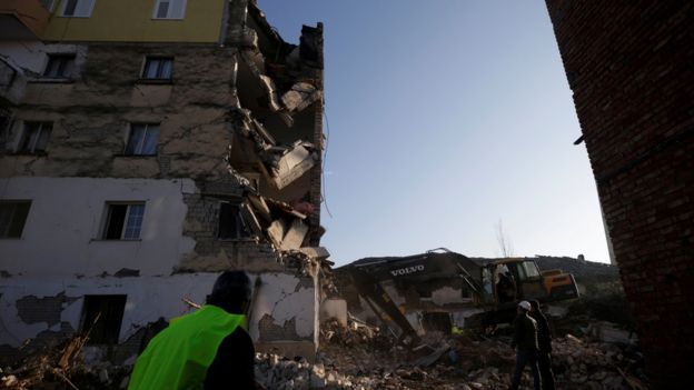 Emergency workers stand in front of rubble