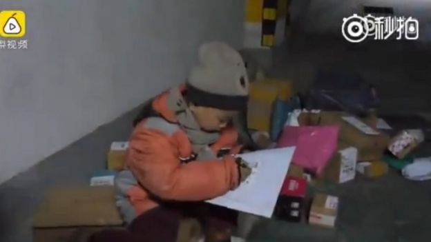 Seven-year-old Chang Jiang reading a parcel list