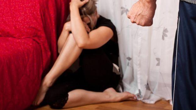 Mujer frente a hombre amenazante.