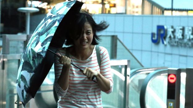 Woman carrying an umbrella battles against strong winds