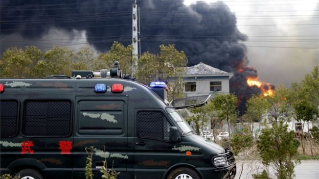 A police van in front of a house with blown out windows, the factory on fire in the background, in Yancheng, China