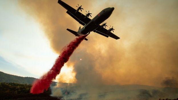 Самолет сбрасывает струю красного цвета