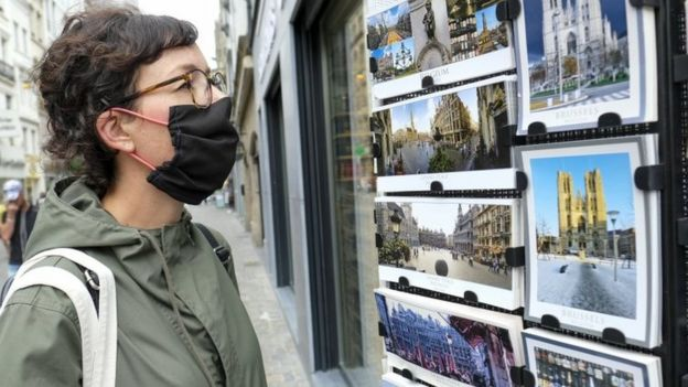 A woman looks at postcards of Brussels in Brussels, Belgium