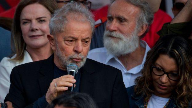 Lula faz discurso após ser libertado na sexta (18), ao lado da namorada e de Gleisi Hoffman