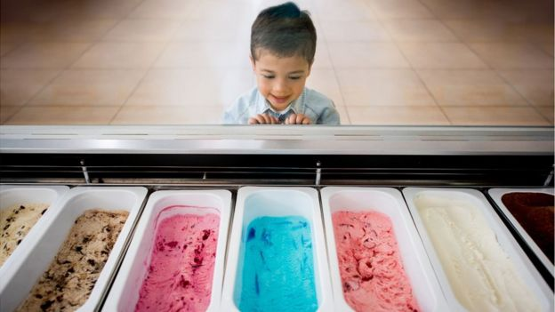 A boy in front of an ice cream cooler