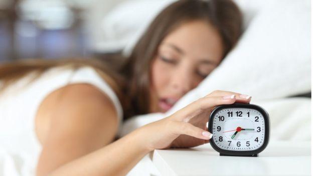 Mulher na cama com despertador.