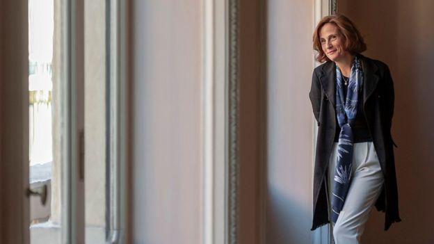 Ilaria Capua sorri, encostada em uma parede de sala requintada