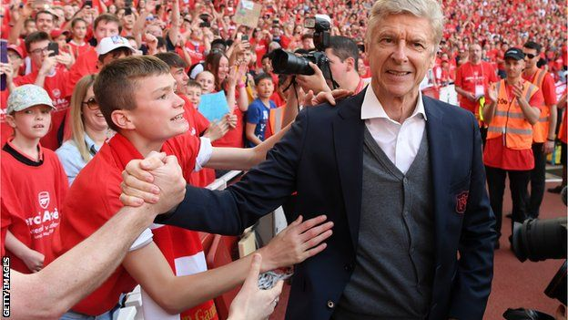 Wenger gives his red club tie to one young fan after his post-match presentation