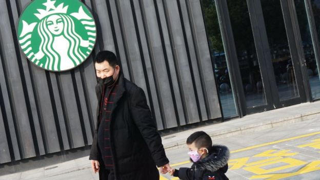 Man with child walks past closed Starbucks in China