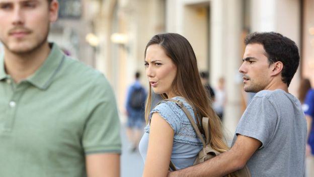 Mujer viendo a otro hombre frente a su pareja.