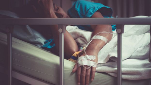 Mujer tumbada en cama de hospital
