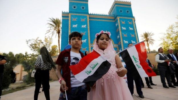 Children hold Iraqi flags during celebrations after Unesco designated Babylon as a World Heritage Site, in front of a replica of Ishtar gate near Hilla, Iraq, July 5, 2019.