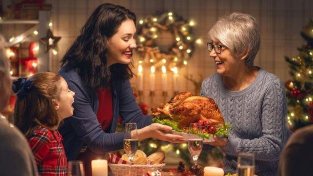 Familia compartiendo comida durante la cena navideña.