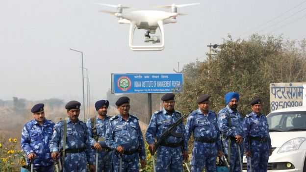 Police stand guard with a hovering drone near a jail where Indian guru and convicted murderer Gurmeet Ram Rahim Singh was being held