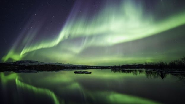 Northern lights blazing over lake Thingvellir national park in Iceland