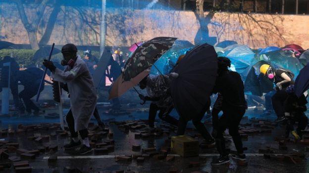 Người biểu tình tự che chắn trước vòi rồng tẩm màu nhuộm xanh của cảnh sát sáng 17/11