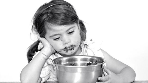 Niña triste comiendo una mezcla de tarta.