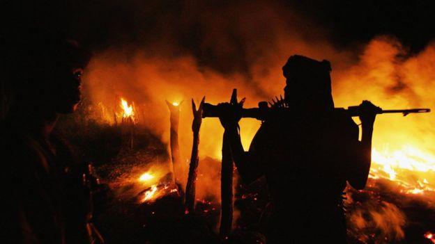 یکی از شبهنظامیان عرب در جنگ دارفور در کنار روستایی که به آتش کشیده شده (سال ۲۰۰۴)